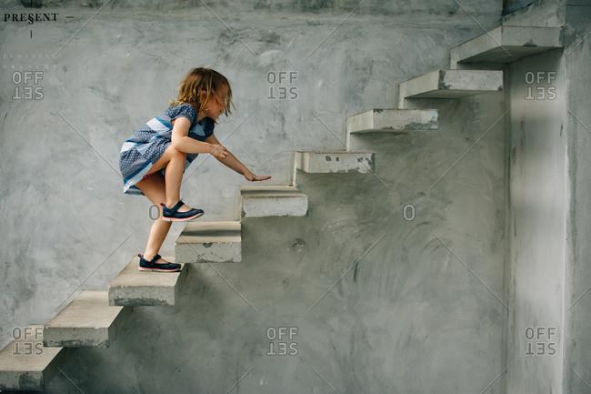 Little girl climbing cement steps