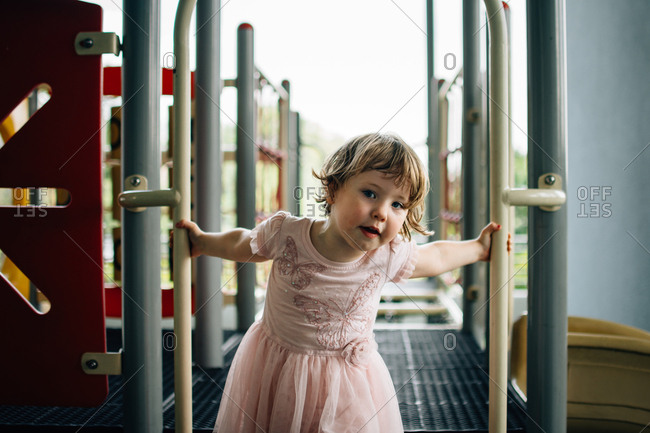 Little girl playing on a play set