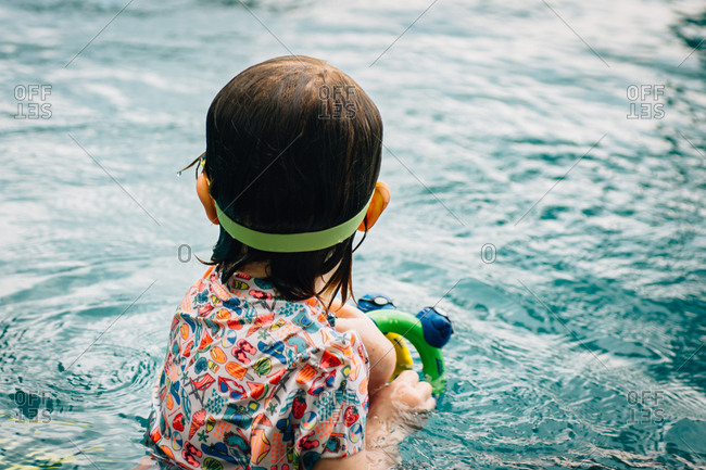 Rear view of girl playing with toys in a swimming pool
