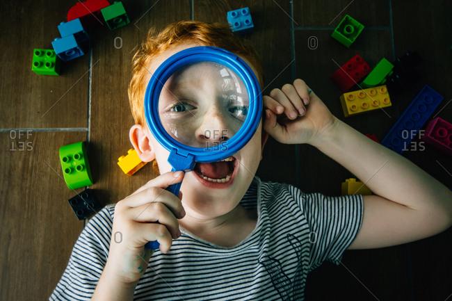 Redhead boy lying on floor looking through magnifying glass