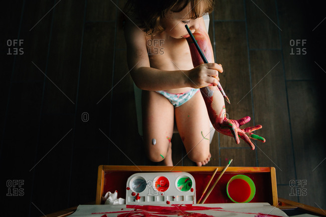 Little girl painting her arms while painting a picture