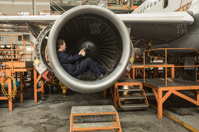 Male aircraft maintenance engineer fixing turbine blade of aircraft at airlines maintenance facility