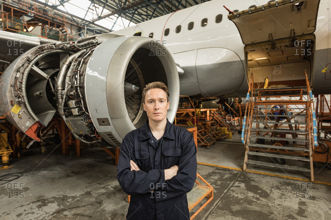 Portrait of male aircraft maintenance engineer standing with arms crossed at airlines maintenance facility