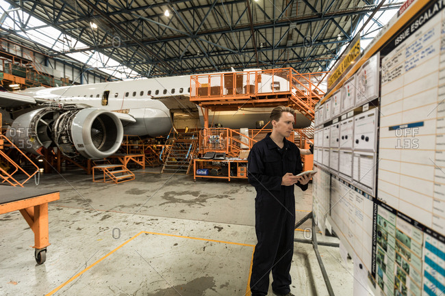 Male aircraft maintenance engineer using digital tablet at airlines maintenance facility