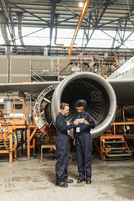Aircraft maintenance engineers discussing over digital tablet at airlines maintenance facility