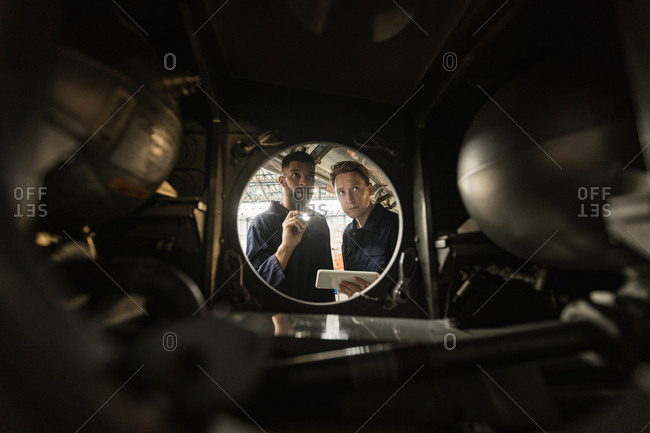 Aircraft maintenance engineers examining engine of an aircraft at airlines maintenance facility