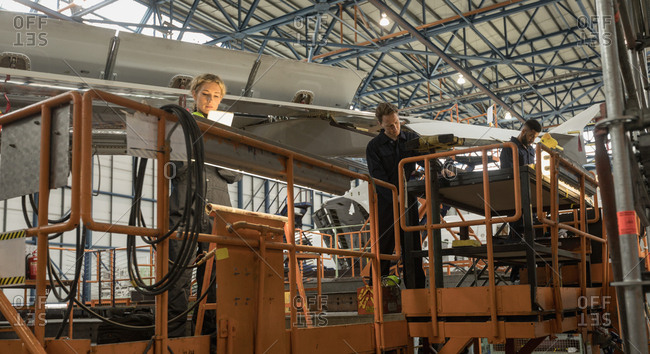 Aircraft maintenance engineers working on aircraft maintenance platform at airlines maintenance facility