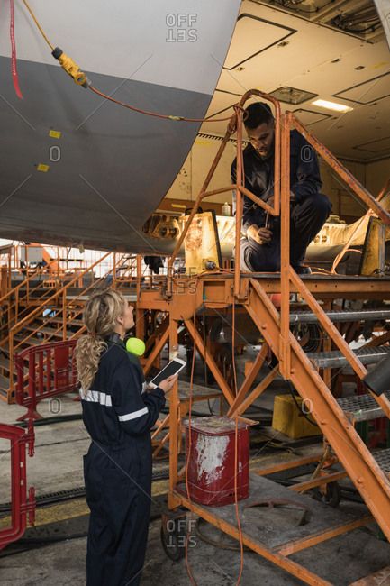 Aircraft maintenance engineers working over an aircraft at airlines maintenance facility
