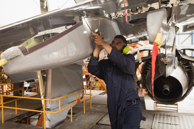 Male aircraft maintenance engineers working over an aircraft at airlines maintenance facility