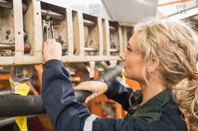 Female aircraft maintenance engineers working over an aircraft engine at airlines maintenance facility