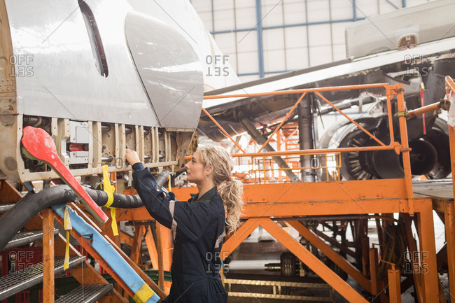 Female aircraft maintenance engineers working over an aircraft at airlines maintenance facility