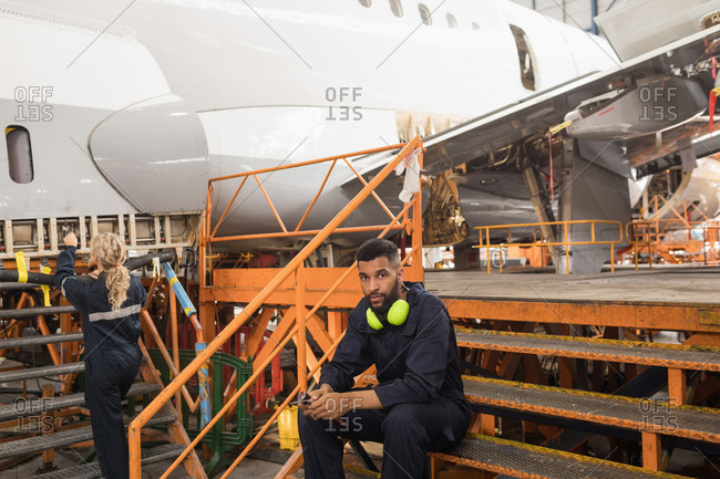 Female aircraft maintenance engineers working over an aircraft while colleague relaxing at airlines maintenance facility