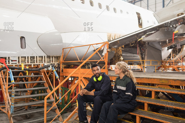 Aircraft maintenance engineers interacting with each other at airlines maintenance facility