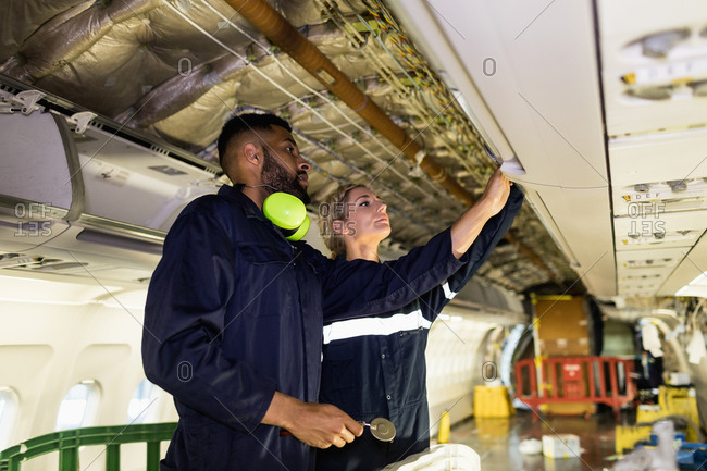 Aircraft maintenance engineers working over internal structure of an aircraft at airlines maintenance facility