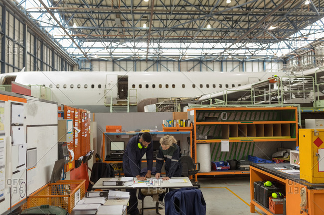 Aircraft maintenance interacting with each other at airlines maintenance facility