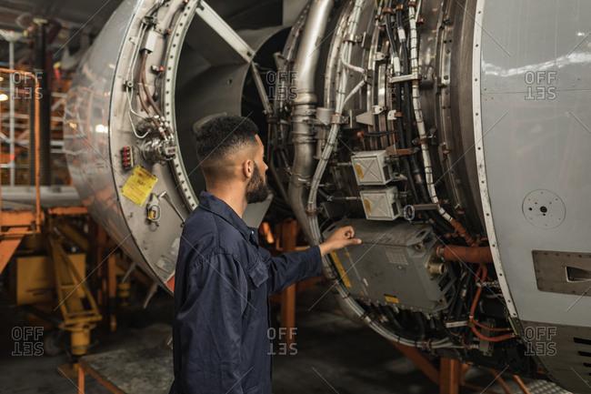 Male aircraft maintenance engineer examining turbine engine of aircraft at airlines maintenance facility
