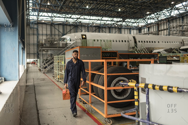 Male aircraft maintenance engineer carrying tool kit at airlines maintenance facility