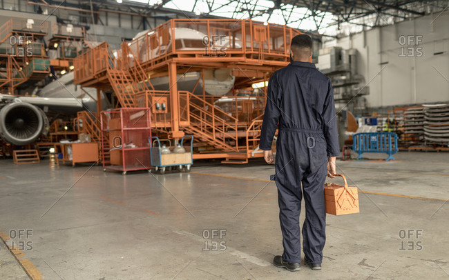 Rear view of male aircraft maintenance engineer holding tool kit at airlines maintenance facility