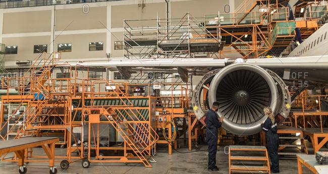Aircraft maintenance engineers examining turbine engine of aircraft at airlines maintenance facility