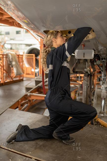 Female aircraft maintenance engineers working over an aircraft engine at airlines maintenance facility