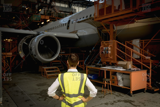 Rear view of female aircraft maintenance engineer standing at airlines maintenance facility