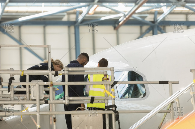Aircraft maintenance engineers working over cockpit of an aircraft at airlines maintenance facility