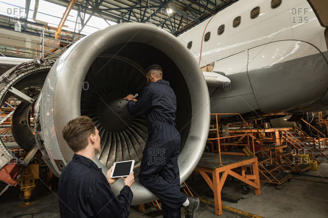 Aircraft maintenance engineers examining turbine engine of aircraft at airlines maintenance facility