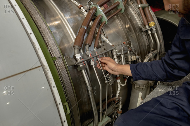 Aircraft maintenance engineer examining turbine engine of aircraft at airlines maintenance facility