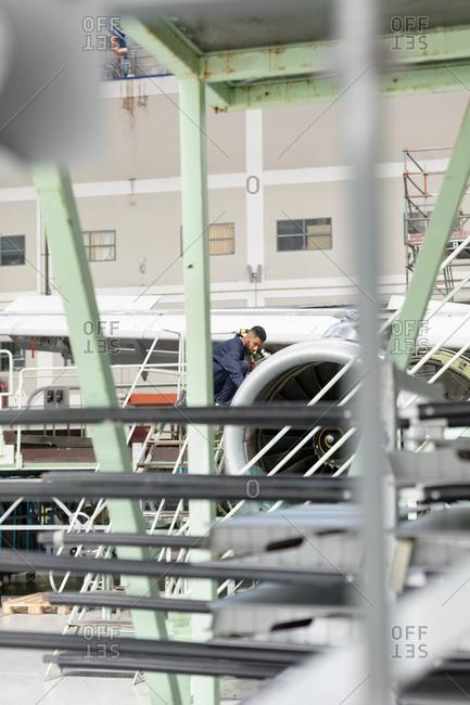 Aircraft maintenance engineer examining turbine engine of aircraft at airlines maintenance facility
