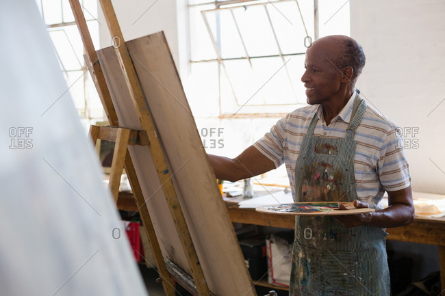 Senior man painting while standing in art class