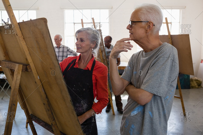 Senior adult looking at woman painting on easel in art