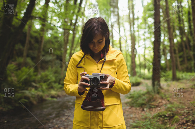 Woman looking clicked photos on vintage camera at forest