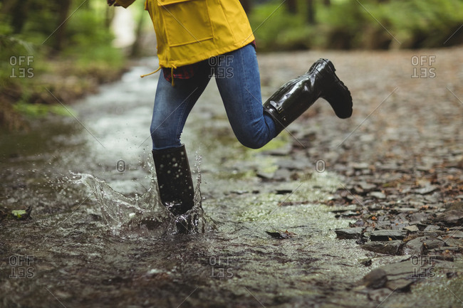 Woman running in water at forest
