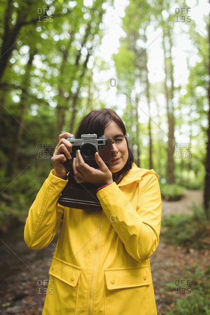 Woman clicking photos of nature in forest
