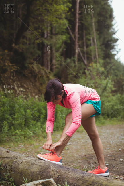 Woman tying her shoe lace in forest