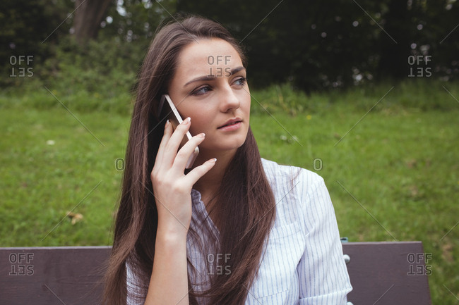 Beautiful woman talking on mobile phone in forest