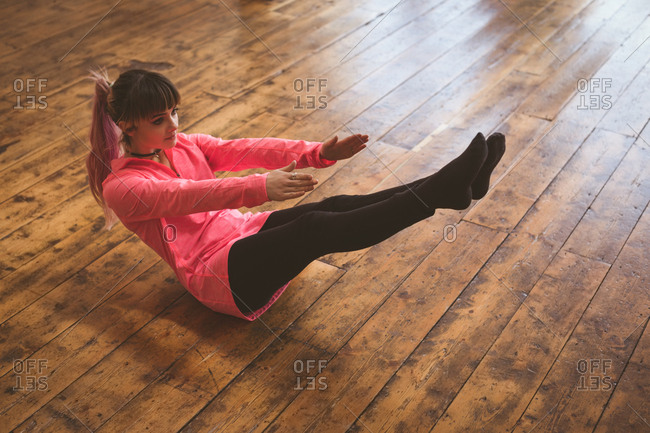 Full length of young woman doing yoga on wooden floor