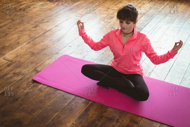 High angle view of woman meditating on exercise mat at yoga studio