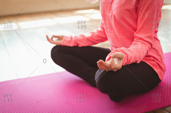 Low section of young woman doing yoga on exercise mat at studio