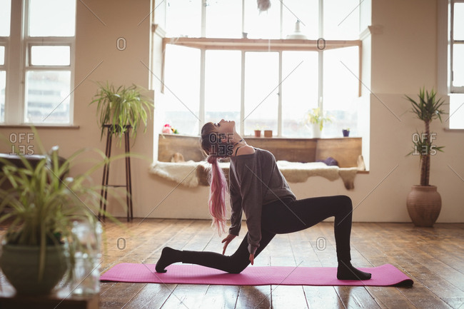 Side view of woman meditating on exercise mat at yoga studio