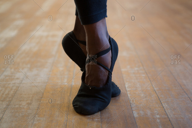 Low section of ballerino practicing ballet dance in the studio