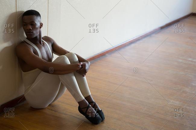 Depressed ballerino sitting against wall in the studio