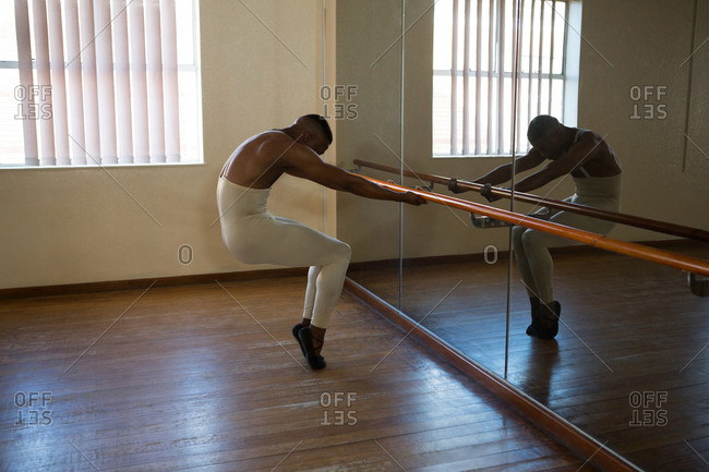 Ballerino stretching on a barre while practicing ballet dance in the studio