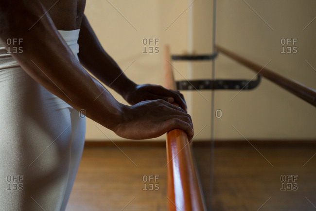 Mid-section of ballerino holding barre