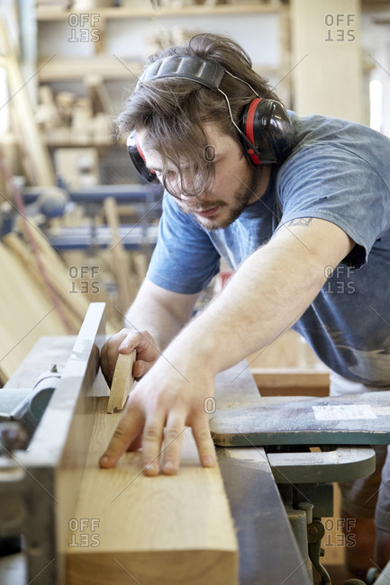 Carpenter wearing ear protection while working in carpentry workshop