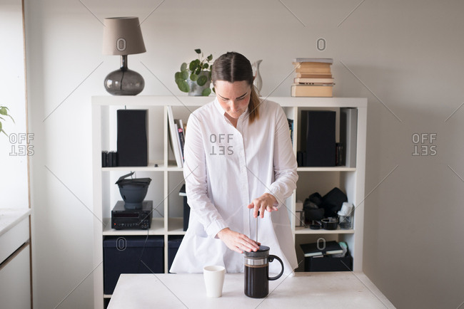Woman using a French press to brew coffee