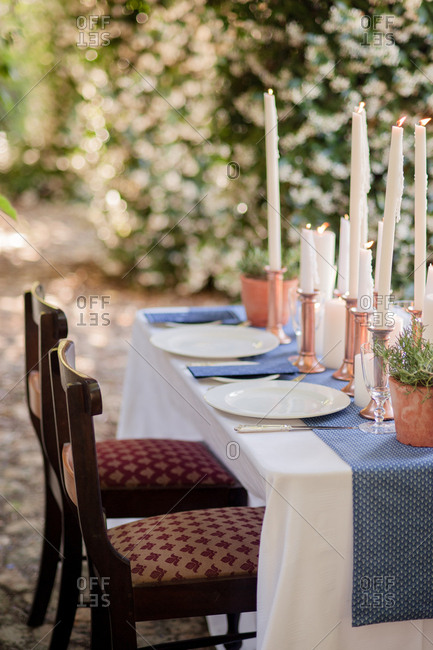 Table decorated with potted plant and taper candles