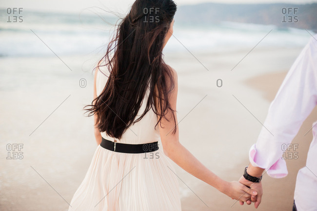 Bride holding hands with groom while walking on the beach