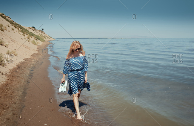 Woman walking along the beach and carrying shoes