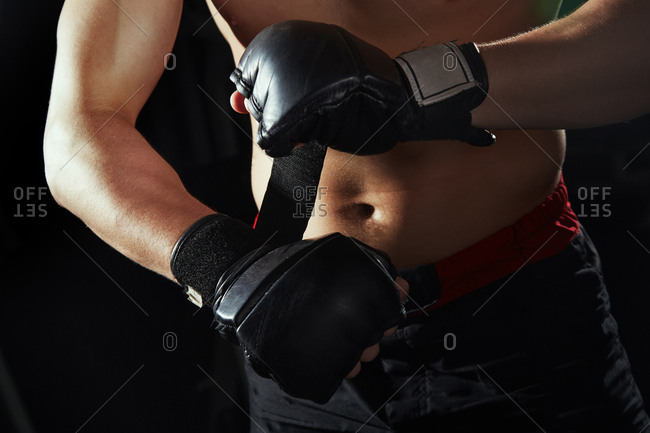 Martial art fighter fastening gloves
